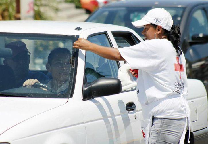 Una voluntaria de la Cruz Roja pega el logo de la institución en un automóvil, luego de que el conductor aportó su granito de arena. (Jesús Tijerina/SIPSE)