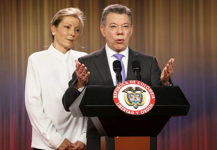 Juan Manuel Santos, presidente de Colombia, llamó a la reconciliación después de ganar el Nobel de la Paz. Le acompaña su esposa, MarÍa Clemencia Rodriguez. (AP/Fernando Vergara)