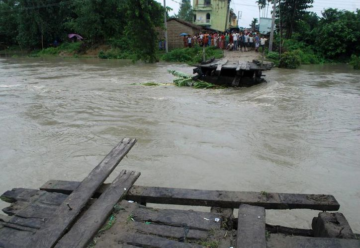 Decenas de personas observan un puente que ha quedado destruido por una riada en Biratnagar, Morang, Nepal. (Archivo/EFE)
