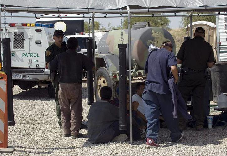 Agentes de la Patrulla Fronteriza de EU procesan a un grupo de inmigrantes detenidos en un puesto de control policía cerca de la frontera con México. (Archivo/EFE)