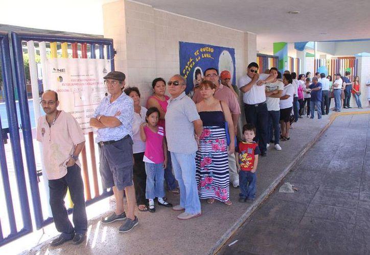 Largas filas se formaron en varias casillas de Mérida, debido al atraso en la apertura, principalmente por problemas con los funcionarios. La imagen es de la casilla ubicada en el Instituto Cumbres de Mérida. (José Acosta/SIPSE)