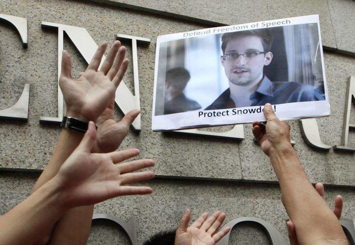 Manifestantes sostienen imágenes y señales de apoyo a Edward Snowden. (Agencias)
