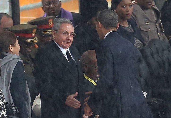 El momento en que Obama saluda de mano a Raúl Castro a su llegada al funeral de Mandela. (Agencias)