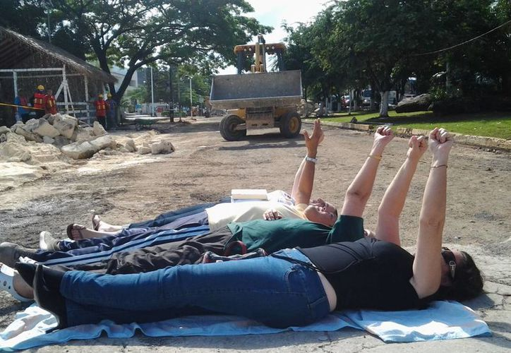 Activistas se tendieron en el pavimento para impedir el paso de la maquinaria, en la avenida Tulum. (Óskar Mijangos/SIPSE)
