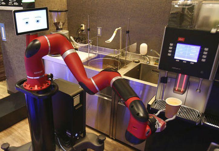 El robot de un solo brazo escanea el boleto de compra de una máquina expendedora. (AP)