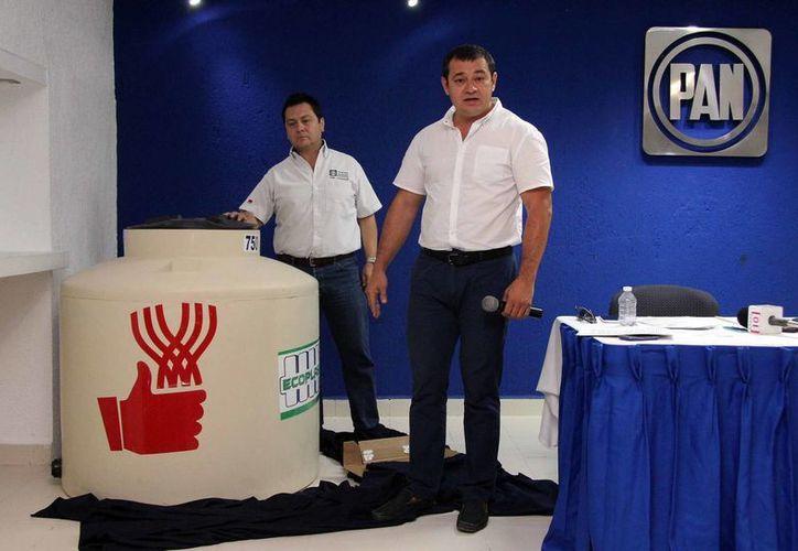 Hugo Sánchez Camargo, presidente estatal del PAN, y Carlos Aldana Herrera, con un tinaco similar a los que reparte el gobierno de Yucatán. (Jorge Pallota/SIPSE)
