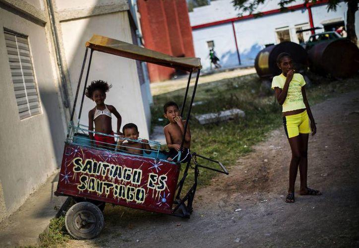 Imagen de unos niños jugando en un carrito de comida vacío estacionado en Santiago, Cuba. (Agencias)