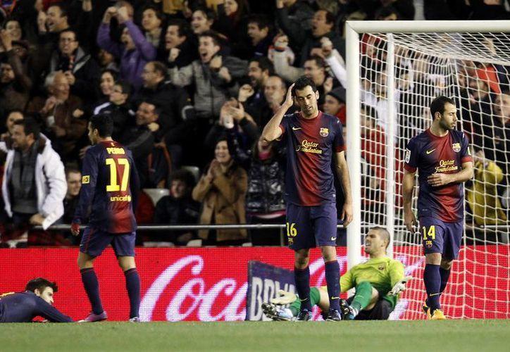 Busquets (centro), el arquero Valdés y Mascherano se lamentan por el gol encajado. (AP)