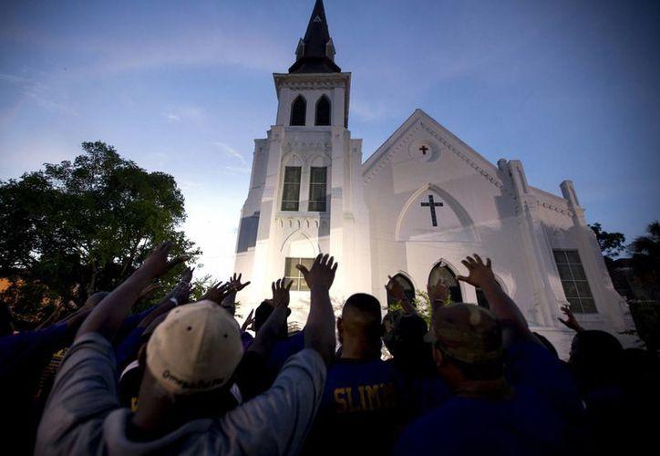 Miles se reunieron fuera de la iglesia donde se registró el tiroteo para orar por las víctimas. (Agencias)