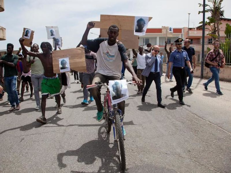 Migrants show pictures of Soumaila Sacko during a protest in San Ferdinando, Italy. Sacko, 29 years-old from Mali, was killed Saturday, June 2, during a shooting Italian investigators said.