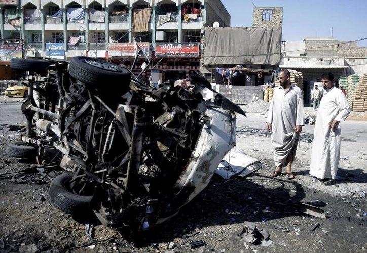 Un grupo de personas observa un coche bomba detonado en el distrito de la Ciudad Sadr, al este de Bagdad, Irak. (EFE/Archivo)