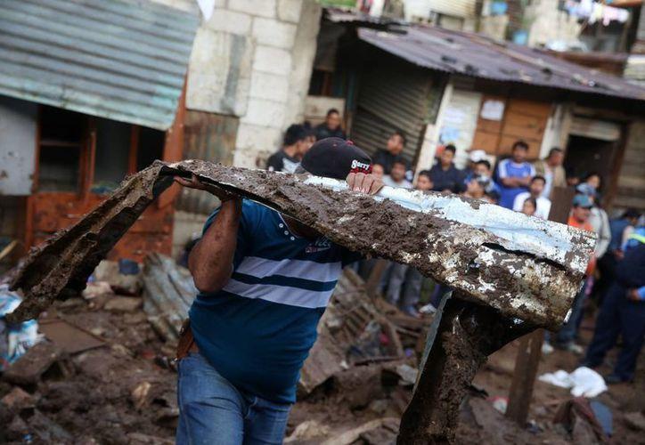 Varias personas colaboran en la remoción de escombros de viviendas destruidas por las copiosas lluvias en Villa Nueva, Guatemala. (EFE)