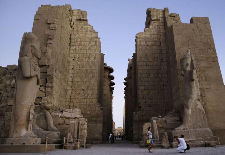 En esta imagen de archivo, una turista posa para una foto en el templo de Karnak, en Luxor, Egipto. Un atacante suicida se hizo explotar aquí, el miércoles 10 de junio de 2015. (AP Fhoto/Hassan Ammar, Archivo)