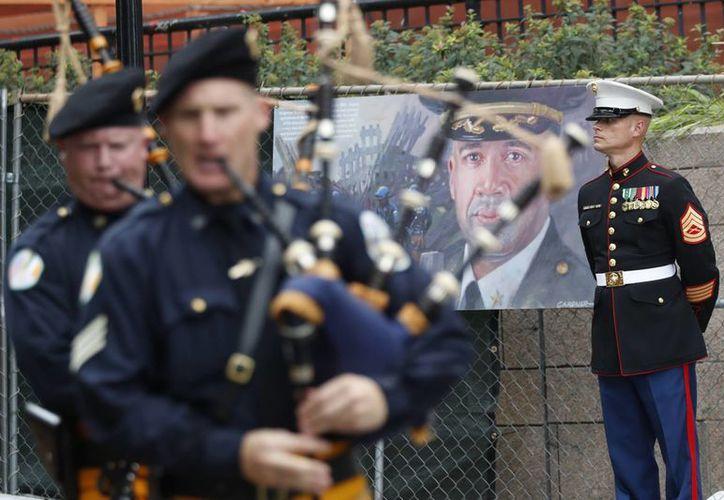 Un miembro del Cuerpo de Marines de Estados Unidos monta guardia junto a la imagen de un policía de Nueva York que murió durante los ataques terroristas del 11 de septiembre de 2001, mientras un grupo de gaiteros marcha durante el desfile en conmemoración del 15to aniversario de los ataques. (AP/Mary Altaffer)
