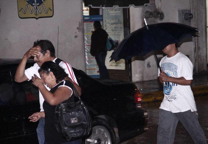 Las lluvias vespertinas materialmente corrieron a las familias que hacían compras de última hora para la cena de Año Nuevo, en el centro de Mérida. (SIPSE)