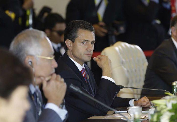 """Peña Nieto (c) durante su participación en la mesa """"Invertir para una economía resistente"""", en la Cumbre de la Apec, en Bali, Indonesia. (Agencias)"""