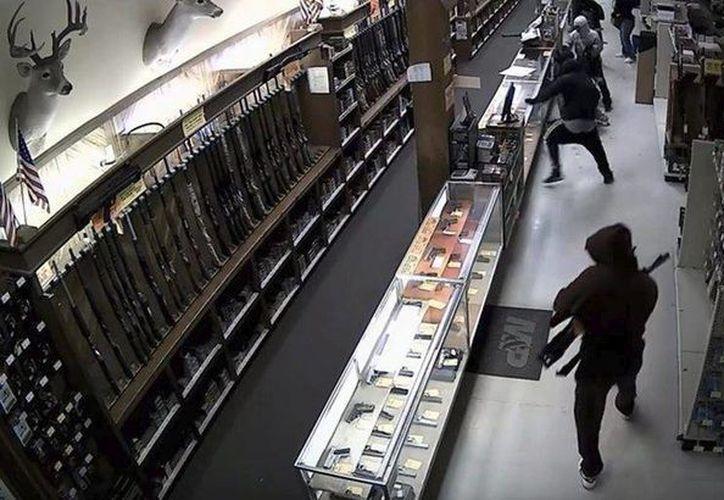 Captura de vídeo que muestra el momento en el que una decena de encapuchados asaltan una tienda de armas en la ciudad de Houston (Texas) llevándose un botín de medio centenar de rifles. (EFE)