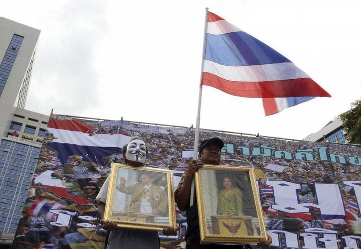 Manifestantes antigubernamentales con fotos del rey tailandés Bhumibol Adulyadej, izquierda, y la reina Sirikit pidiendo al primer ministro Yingluck Shinawatra que retire un proyecto de ley de amnistía del parlamento, en Bangkok. (Agencias)