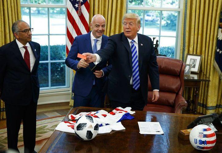 Gianni Infantino, presidente de la FIFA, regaló a Donald Trump tarjetas rojas y amarillas, durante su visita a la Casa Blanca. (AP)