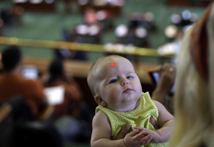 Zoey Pulte lleva un punto naranja en la frente mientras ella y su madre, Amanda, que se opone a una ley de aborto, escuchar al senador Wendy Davis. (Agencias)