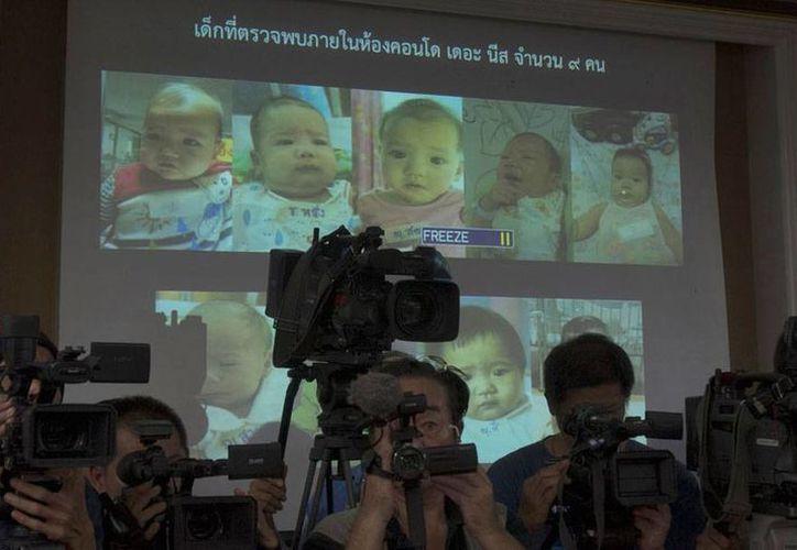 Aspecto de la rueda de prensa en la que se informó de la 'fábrica de bebés' que un empresario japonés montó en varios países de Asia. Atrás de los reporteros gráficos pueden verse fotos de los bebés que engendró Mitsutoki Shigeta. (AP)