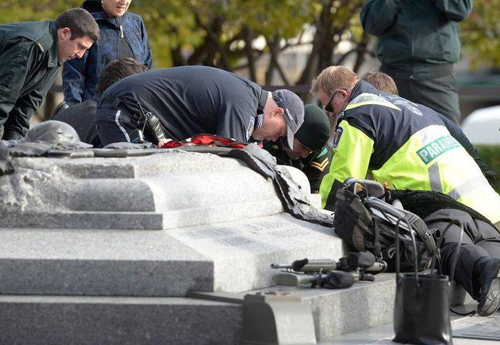 Cuerpos de rescate atienden a un soldado que recibió disparos de un desconocido, cerca del Parliament Hill (sede del Parlamento), en Ottawa, Canadá). (AP)
