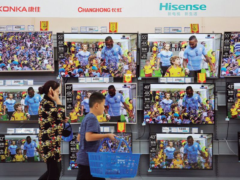 Woman and a child pass Chinese brands of flat screen TVs on display at a hypermarket in Beijing.