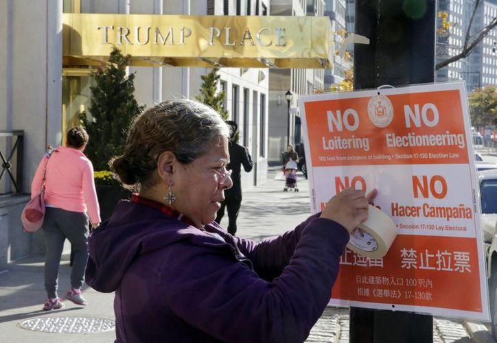 Imagen del 8 de noviembre de 2016, de una mujer que coloca un anuncio afuera de un edificio de con el nombre de Donald Trump, en Nueva York. Este es uno de los edificios al que será retirado el nombre del presidente electo de EU, por petición de los inquilinos. (AP/Richard Drew)
