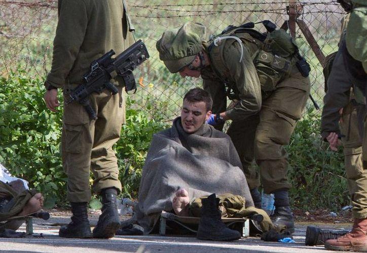 Elementos del Ejército de Israel atienden a uno de sus compañeros heridos, tras el ataque de Hezbolá al convoy militar judío. (AP)