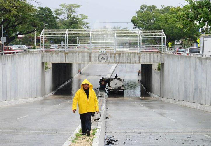 El paso a desnivel en Circuito Colonias fue cerrado desde las primeras horas de ayer y hasta la noche ya se habían desaguado poco más de 200 mil litros de agua. (Milenio Novedades)