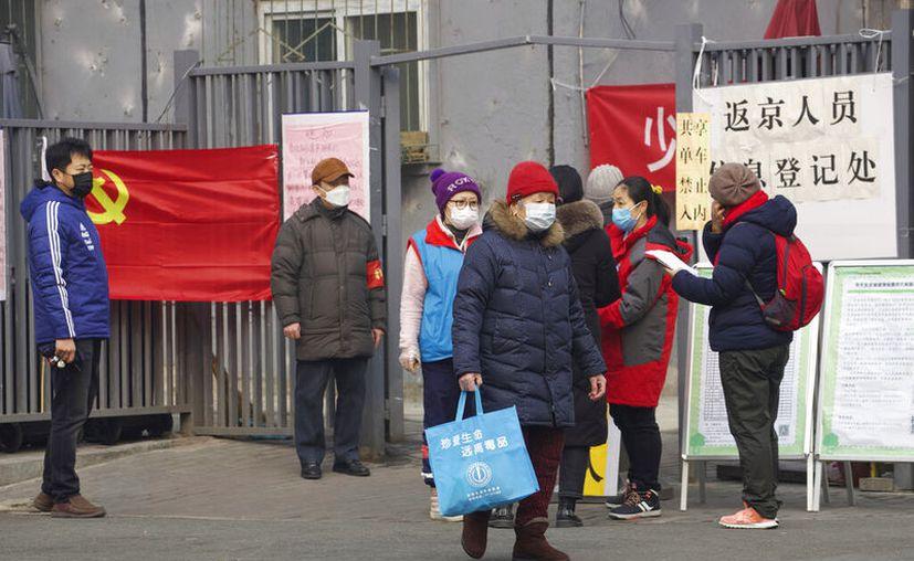 """Residentes esperan para entrar a un punto de control que dice """"punto de registro para personas que regresan a Beijing"""" en Beijing, China, el jueves 13 de febrero de 2020. (AP Foto/Ng Han Guan)"""