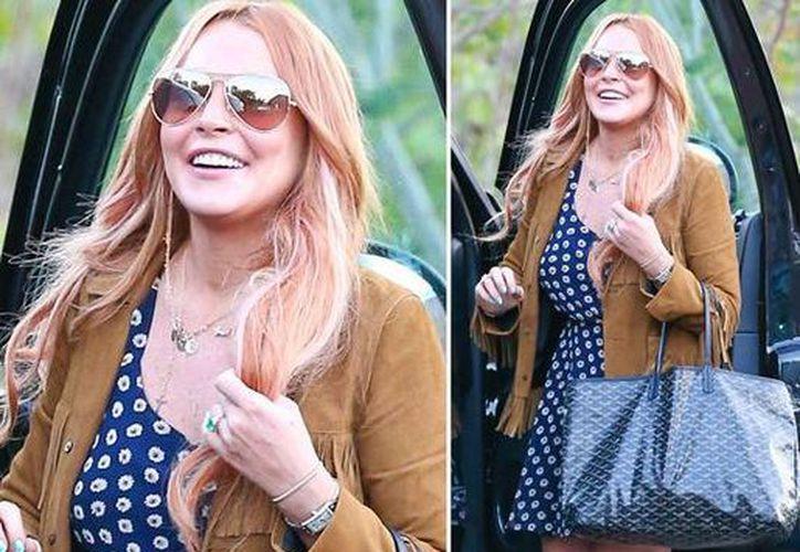 Una foto muestra a Lindsay Lohan en la que se ve a la actriz sonriendo antes de subirse a un coche tras haber salido del centro Cliffside. (tmz.com)