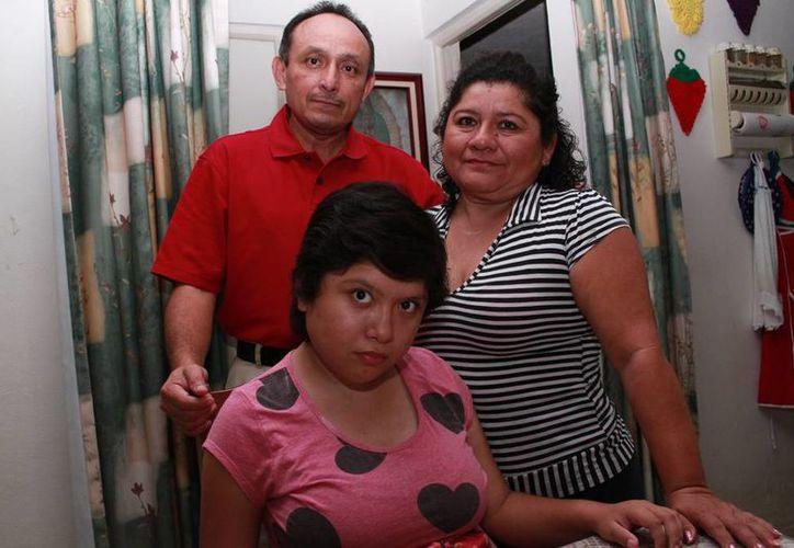 Alondra, acompañada de sus padres Francisco Peña Herrera y Lizbeth Pech Estrella, quienes juntos han luchado por una mejor calidad de vida para la joven quien sufre de epilepsia refractaria. (Jorge Acosta/ Milenio Novedades)