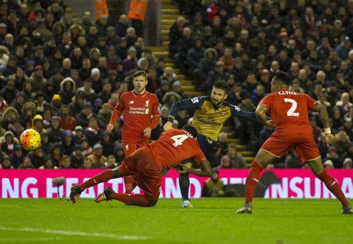 El francés Olivier Giroud al marcar un de los dos goles con los que el Arsenal empató a tres contra el Liverpool en su visita al Anfield Stadium. (AP)