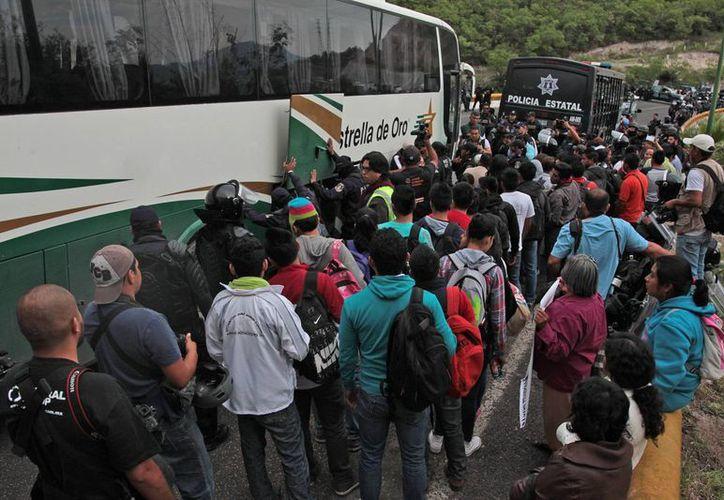 Alumnos de la Normal Rural de Ayotzinapa que se dirigían a Chilpancingo son revisados por la policía estatal en la carretera que une Tixtla con la capital. El jueves, en Guerrero se registraron hechos violentos que enrarecen el clima electoral. (EFE)