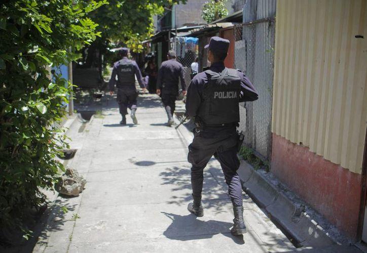 Agentes de la Policía Nacional Civil (PNC) brindan seguridad en una comunidad con alta presencia de pandillas en San Salvador. Esta semana, la Corte Suprema facultó a los jueces a procesar pandilleros como terroristas(EFE/Archivo)