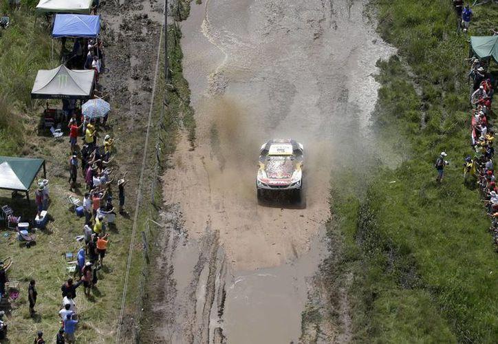 Los pilotos Stephane Peterhansel y Jean Paul Cottret en un mismo vehículo en el inicio del Rally Dakar. El ganador de la primera etapa fue un hombre de Catar, Nasser Al Attiyah. (Fotos: AP)