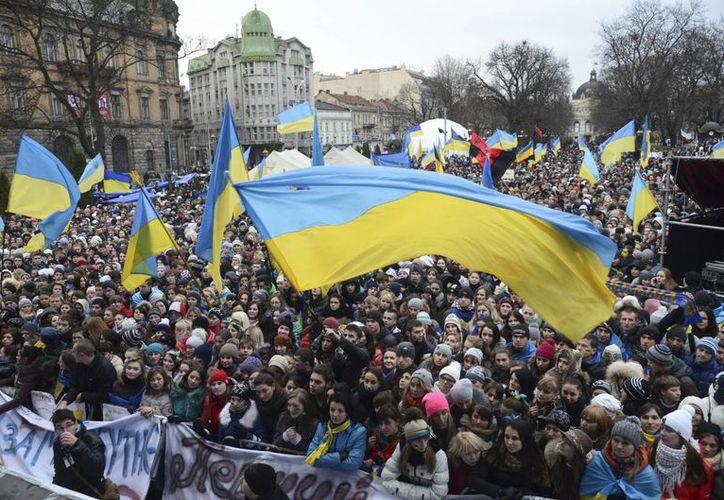 Una multitud ondea la bandera ucraniana y de la Unión Europea durante una manifestación de apoyo al ingreso de Ucrania en la UE. (Agencias)