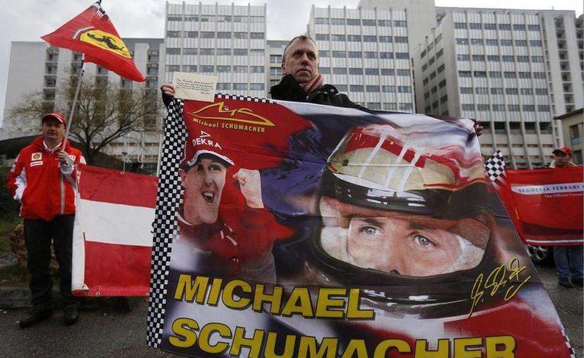 Seguidores de Michael Schumacher se reúnen afuera del hospital francés de Grenoble, Francia, donde permanece en un coma inducido, para darle ánimos. (EFE)
