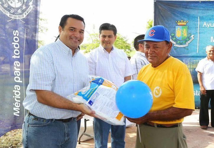 El alcade Renán Barrera Concha entrega un mosquitero a Felipe Padrón Ochoa. (Cortesía)