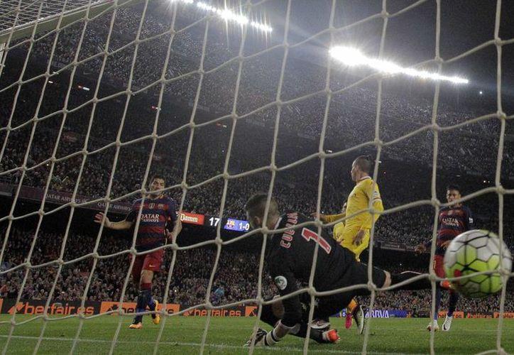 Con su poker ante Gijón Luis Suárez (i) se convirtió este sábado en el primer jugador en la historia de la Liga de España en meter 4 goles en dos partidos al hilo. (AP)