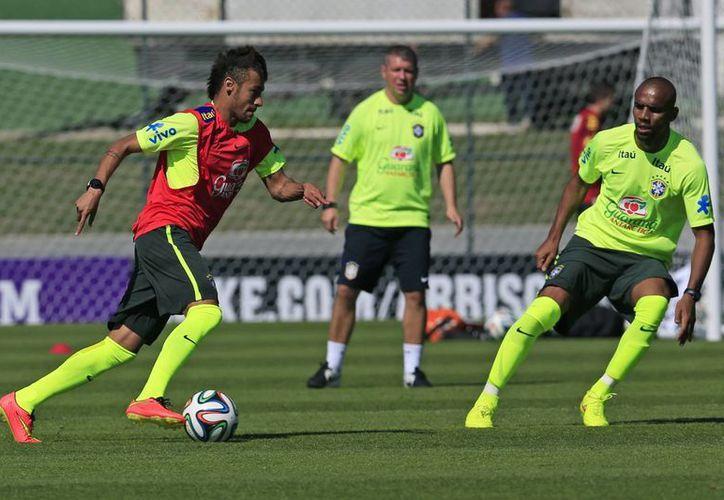 Neymar lucha por el balón con Maicon en un entrenamiento de Brasil como parte de su preparación para el Mundial que comienza el próximo jueves en ese país. (Foto: AP)