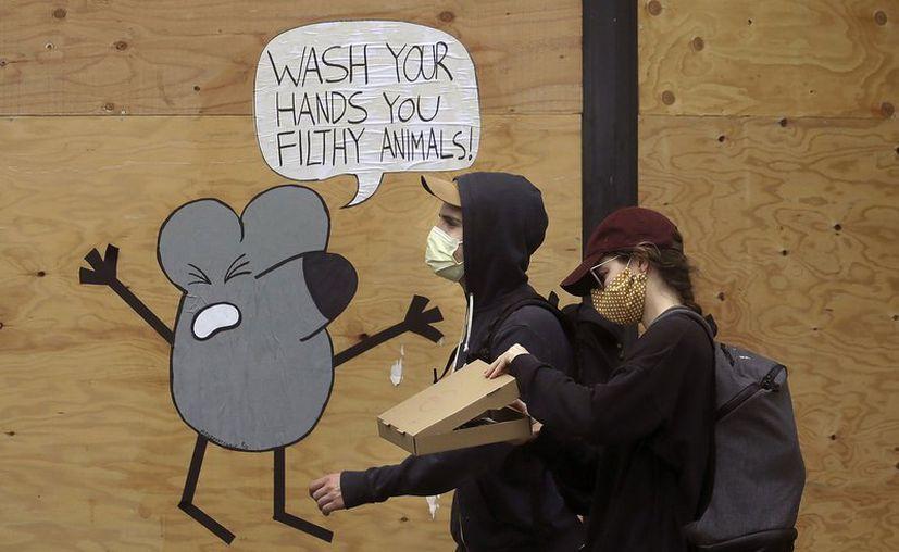 Dos jóvenes con mascarillas pasan junto a un mural que recuerda a la gente que se lave las manos, en San Francisco. (Foto: AP).