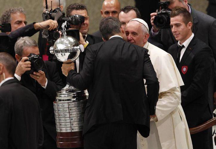 Momento en que un integrante del club de futbol San Lorenzo se acerca al Papa Francisco para entregarle la réplica de la Copa Libertadores. (Agencias)