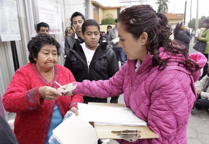 En la imagen, ciudadanos hacen fila para tramitar su credencial para votar. (Archivo/Notimex)