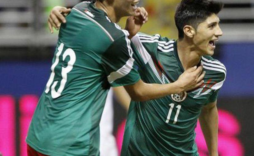El defensa Diego Reyes (i) felicita a Alan Pulido, que tuvo una noche inolvidable con el Tri al marcar tres tantos. (Notimex)