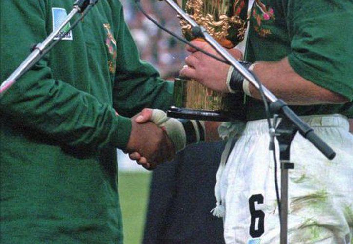 En esta imagen del 24 de junio de 1995, el presidente Nelson Mandela entrega la Copa del Mundo de Rugby a Francois Pienaar, capitán de la selección sudafricana, tras vencer a Nueva Zelanda. (Agencias)