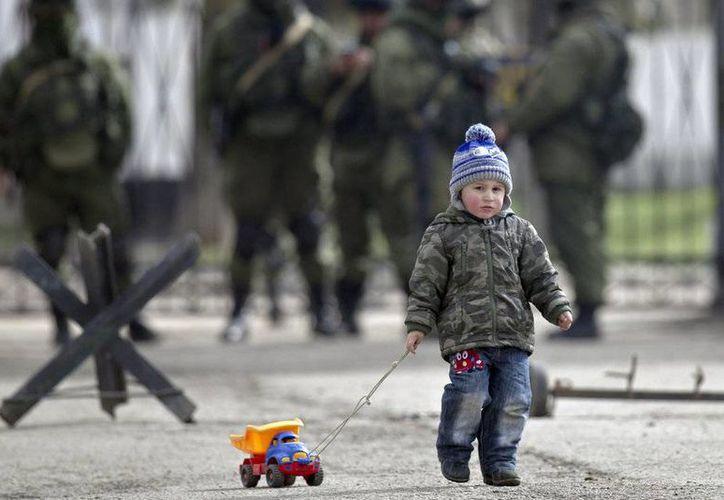 Un niño pasea un coche de juguete delante de soldados prorrusos en la zona exterior de la base militar ucraniana en Perevalne, Crimea Vadim Ghirda. (AP)