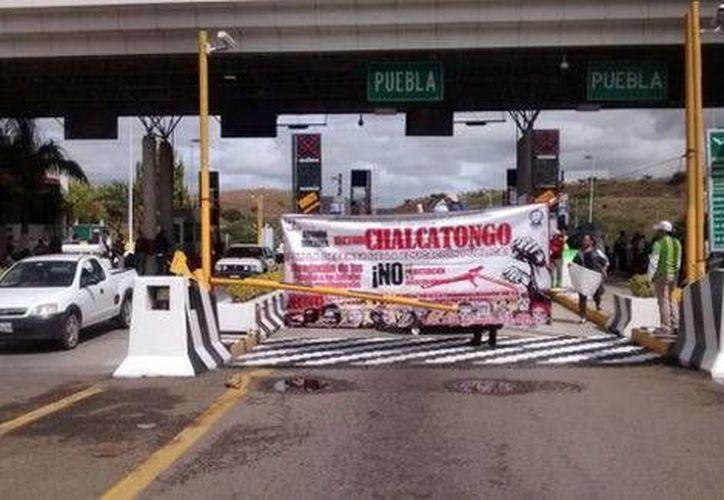 Los maestros manifestantes de ña CNTE permiten el libre peaje con su respectiva cuota en una de las casetas de la autopista Oaxaca-México. (Milenio)