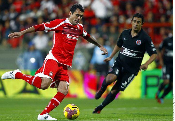 Dueñas saca el balón ante la presión de Moreno (negro). (Agencia Reforma)
